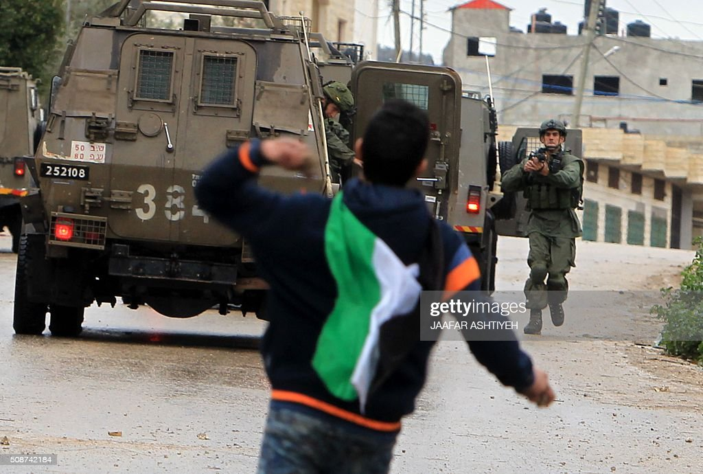 A Palestinian youth throws stones towards Israeli military vehicles in the village of Qabatiya, near the West Bank town of Jenin, during clashes on February 6, 2016. Three Palestinians from Qabatiya attacked Israeli police with guns and knives outside Jerusalem's Old City, on February 3, killing a female officer and wounding another before being shot dead. ASHTIYEH