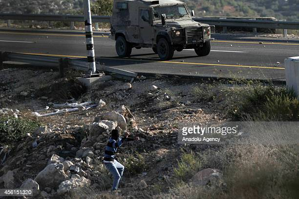 Palestinian youth throws stones towards Israeli soldiers during clashes following a protest against the expropriation of Palestinian land by Israel...