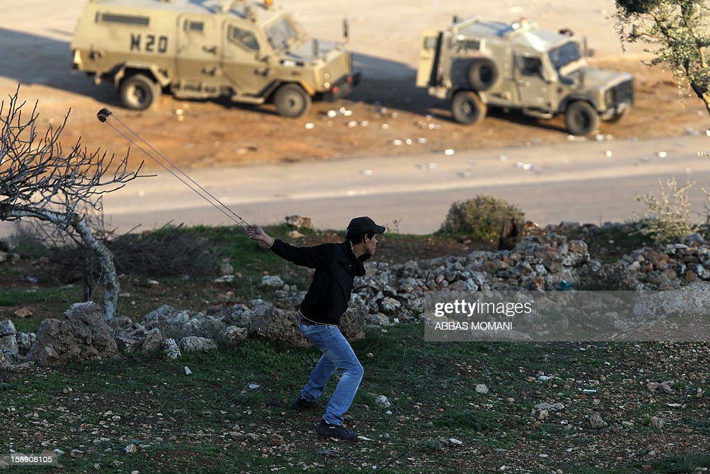 A Palestinian youth throws stones using a sling shot at Israeli soldiers at the entrance to Israel's Ofer military prison, near the West Bank village of Betunia, following a demonstration in support of Palestinian prisoners on hunger strike in Israeli jails and calling for their immediate release on January 3, 2013. AFP PHOTO/ABBAS MOMANI