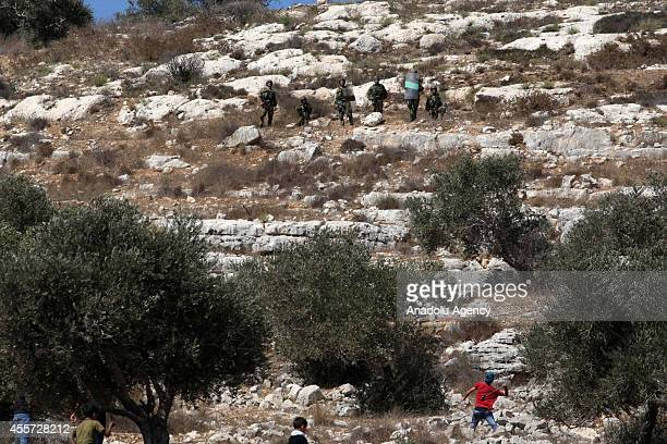 Palestinian youth uses a slingshot to hurl stones towards Israeli soldiers during clashes following a protest against the Jewish settlements and the...