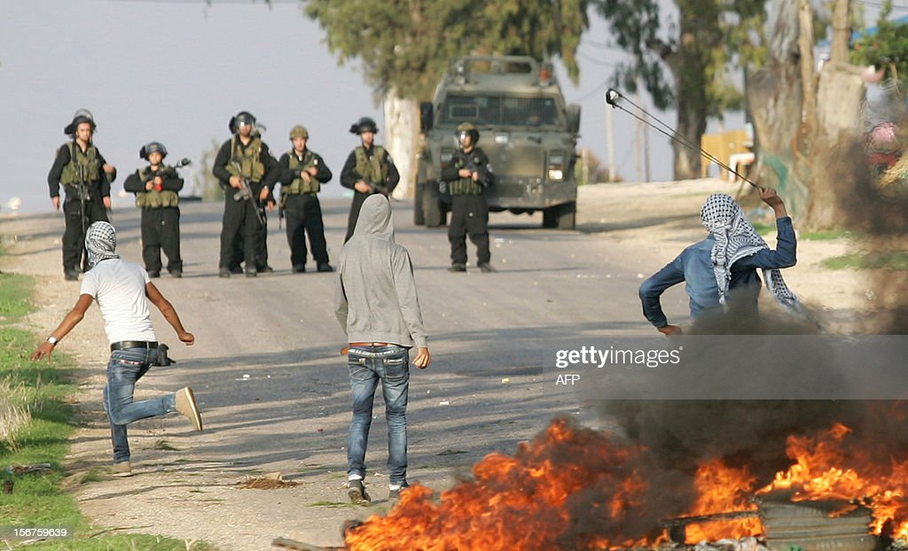 A Palestinian youth uses a slingshot to throw stones at Israeli security forces during clashes at the Jalama checkpoint near the West Bank city of Jenin, on November 20, 2012, following a demonstration against the ongoing Israeli military offensive on the Gaza Strip. Clashes erupted as thousands of Palestinians marched demanding revenge for the killing of a Palestinian protester the day before.