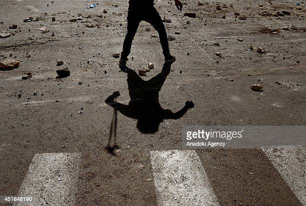 Palestinian youth uses slingshot tu hurl stones at Israeli security forces during the clashes over the abduction and killing of a Palestinian teen by...