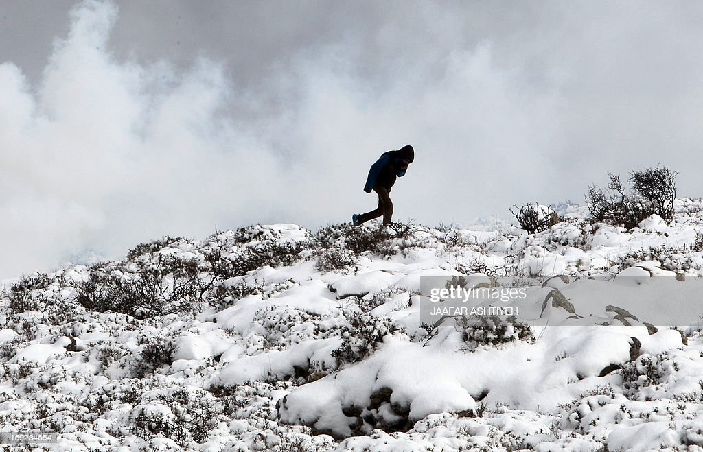 A Palestinian youth walks on a snow covered hill while protecting his face from tear gas during clashes with Israeli forces after Israeli settlers from the nearby Esh Kodesh settlement cut Palestinian farmers' olive trees on January 10, 2013 in village of Qusra, south of the city of Nablus. Israeli settlers opened fire in the northern West Bank wounding two Palestinians in separate incidents, Palestinian security forces and witnesses said.