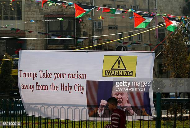 A Palestinian youth walks past a protest banner in the West Bank city of Nablus bearing an image of US Presidentelect Donald J Trump and a slogan...