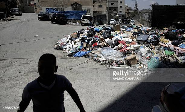A Palestinian youth walks past piles of accumulated rubbish in the Palestinian refugee camp of Shuafat in east Jerusalem on June 12 2015 The refugee...