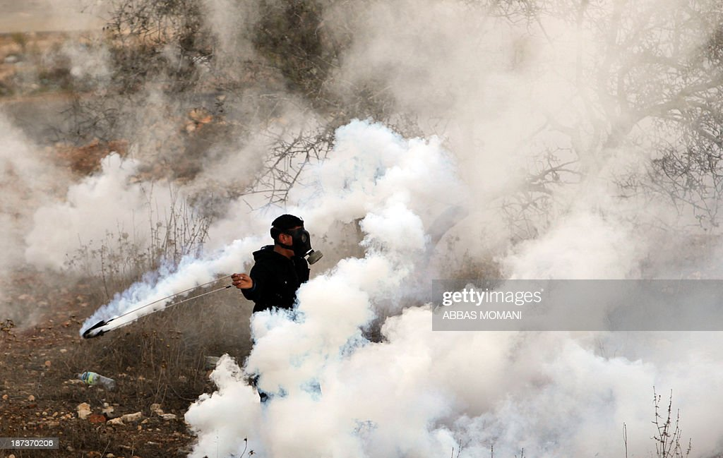 A Palestinian youth wearing a gas mask to protect himself from tear gas, lobs a stone during clashes with Israeli soldiers close to the Israeli Ofer military prison, near the West Bank village of Betunia, on November 8, 2013. The clashes errupted a day after Israeli forces killed a Palestinian near Jerusalem, Israeli police and family members said, as the United States warned of a third intifada if Middle East peace talks fail.