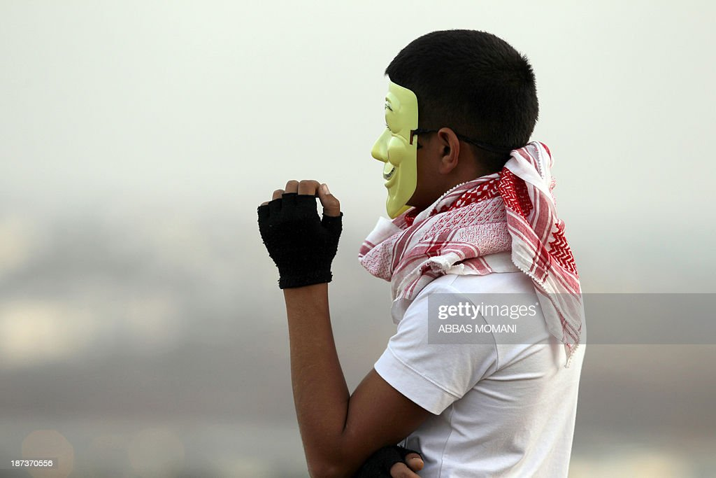 A Palestinian youth wears a mask of the Anonymous movement during clashes with Israeli soldiers close to the Israeli Ofer military prison, near the West Bank village of Betunia, on November 8, 2013. The clashes erupted a day after Israeli forces killed a Palestinian near Jerusalem, Israeli police and family members said, as the United States warned of a third intifada if Middle East peace talks fail.