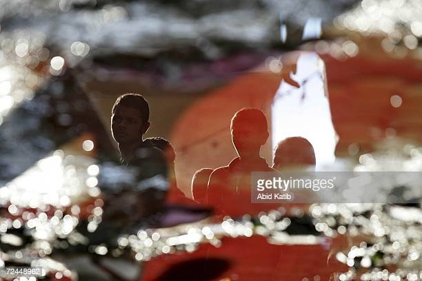 Palestinian youths are reflected in water stained with blood after Israeli tanks fired on homes in Beit Hanoun November 8 2006 in Beit Hanoun in the...