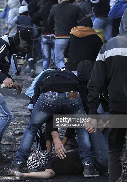 Palestinian youths assist a fellow protester after he was injured during clashes with Israeli security forces in the Palestinian refugee camp of...