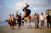 Palestinian youths backflip on the beach in Gaza City on Septemper 4 2013 AFP PHOTO /MOHAMMED ABED