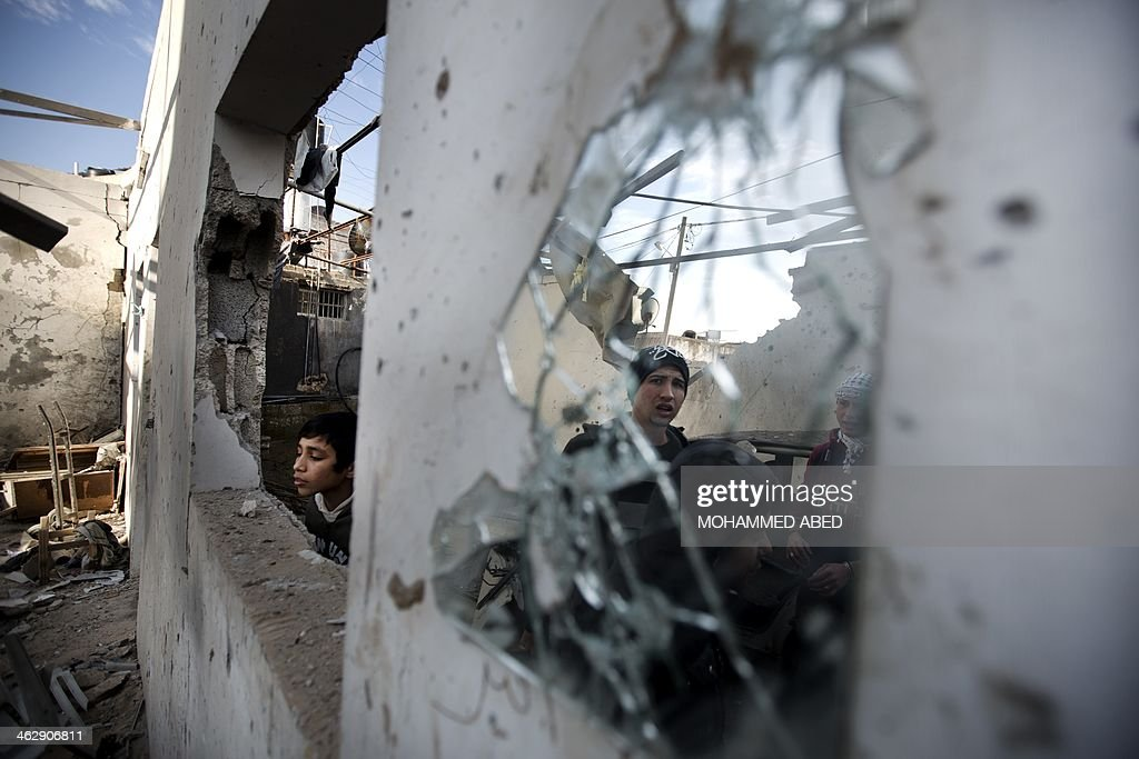 Palestinian youths check a destroyed building following overnight Israeli air strikes in Gaza City on January 16, 2014. Israeli air strikes in the Gaza Strip against training camps used by the armed wing of the territory's Hamas rulers left four children and a woman wounded, Palestinian medical sources said. AFP PHOTO/MOHAMMED ABED