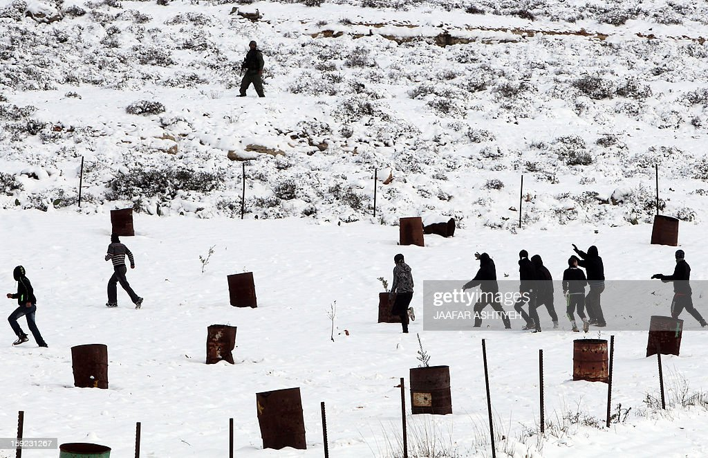 Palestinian youths clash with Israeli forces under snowfall after Israeli settlers from the nearby Esh Kodesh settlement cut Palestinian farmers' olive trees on January 10, 2013 in village of Qusra, south of the city of Nablus. Israeli settlers opened fire in the northern West Bank wounding two Palestinians in separate incidents, Palestinian security forces and witnesses said.