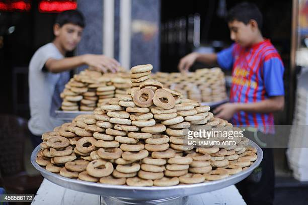 Palestinian youths display sweets outside a shop in Gaza City on October 3 on the eve of the Muslim holiday of Eid alAdha or Feast of the Sacrifice...