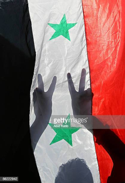 Palestinian youths flash Vsigns while they hold Syrian flags during a proSyrian demonstration November 18 2005 in Gaza City Gaza Strip Hundreds of...