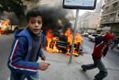Palestinian youths flee while gunmen open fire into the air in front of burning vehicles belonging to the local electricity company on December 20...