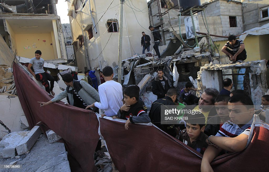 Palestinian youths gather outdoors in a heavily damaged neighbourhood following overnight Israeli air strikes in the southern Gaza Strip, one of them targeting the house of Hamas commander Raed al-Attar, in Rafah on November 20, 2012. The Israeli military said it attacked about 100 targets in the coastal strip during the night, using aircraft, warships and artillery. AFP PHOTO/ SAID KHATIB