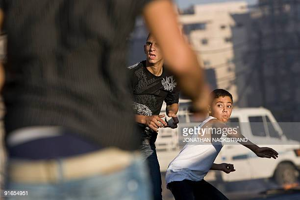 Palestinian youths hurl stones at Israeli forces during clashes on October 5 2009 in the east Jerusalem Shuafat refugee camp Police flooded into...