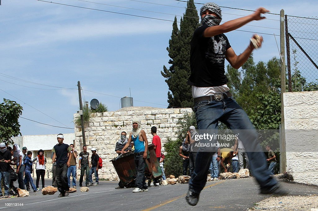 Palestinian youths hurl stones at Israeli troops during clashes following a demonstration in the West Bank village of Nabi Saleh on May 21, 2010 against the expansion of the nearby Jewish settlement of Halamish . Israeli forces shot dead two Palestinian gunmen who had just infiltrated Israel from the Gaza Strip, the military said.