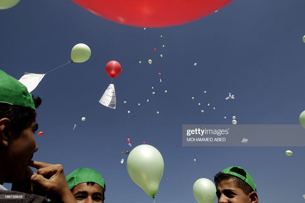 Palestinian youths launch balloons in the air during a gathering is solidarity with Palestinian prisoners held in Israeli prisons, in Gaza City on April 16, 2013. Statistics published by Israeli rights group B'Tselem show by the end of 2012, some 4,500 Palestinians were being held in Israeli jails. AFP PHOTO/MOHAMMED ABED