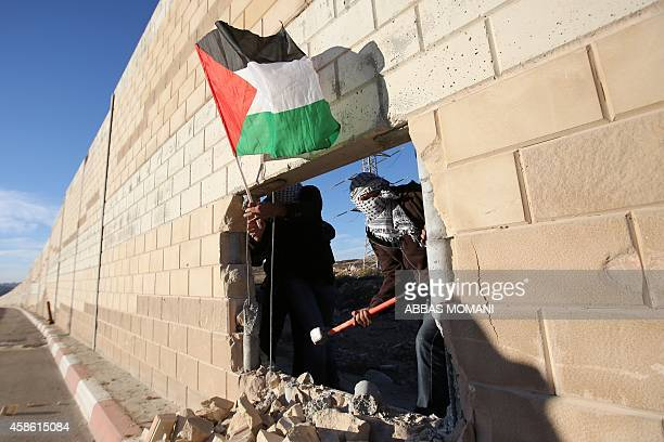 Palestinian youths one holding a national flag appear through a hole they dug in the controversial Israeli separation wall in the West Bank village...
