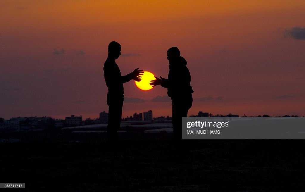 Palestinian youths play as the sun sets in Beit Hanun in the northern Gaza Strip on April 9, 2014. AFP PHOTO/MAHMUD HAMS