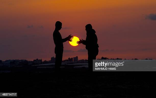 Palestinian youths play as the sun sets in Beit Hanun in the northern Gaza Strip on April 9 2014 AFP PHOTO/MAHMUD HAMS