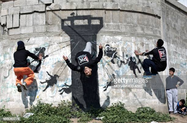 Palestinian youths practice their Parkour skills on a mural said to have been painted by British street artist Banksy showing children swinging on an...