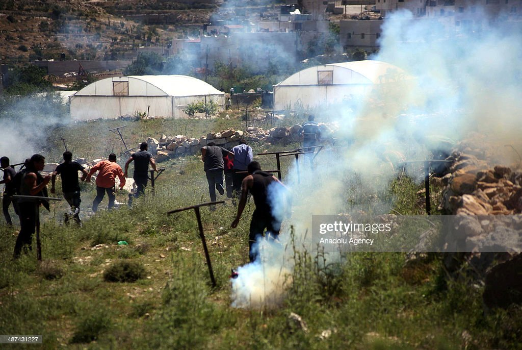 Palestinian youths run for cover from tear gas fired by Israeli soldiers during a protest against the demolition of two houses by Israeli bulldozers on April 30, 2014 in Al-Aroub refugee camp near Hebron. Israeli bulldozers backed by army troops on Wednesday demolished two houses in the Al-Aroub refugee camp near the West Bank city of Al-Khalil (Hebron).