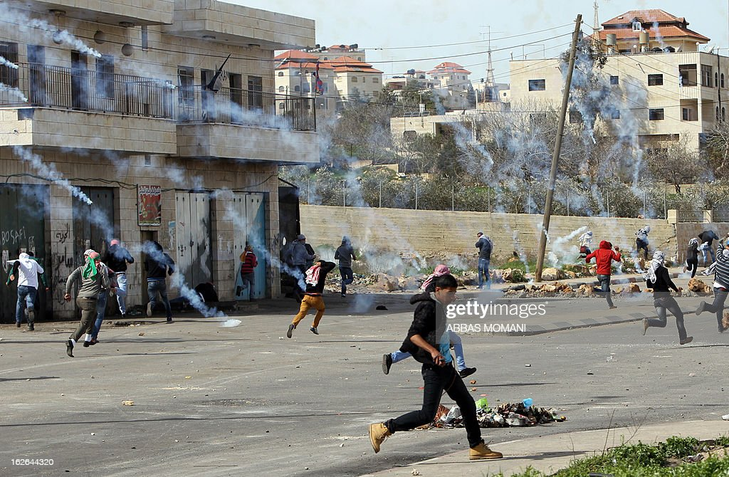 Palestinian youths run for cover from tear gas smoke fired by Israeli forces during clashes outside Israel's Ofer prison near Ramallah on February 25, 2013 after a protest in support of Palestinian prisoners on hunger strike in Israeli prisons. Palestinian president Mahmud Abbas said that Israel was deliberately seeking to stoke unrest in the occupied West Bank but that Palestinians would not be provoked. AFP PHOTO/ABBAS MOMANI