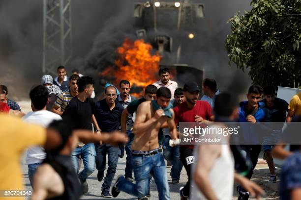 TOPSHOT Palestinian youths run from the path of an Israeli army bulldozer during clashes in the village of Kobar west of Ramallah on July 22 as...