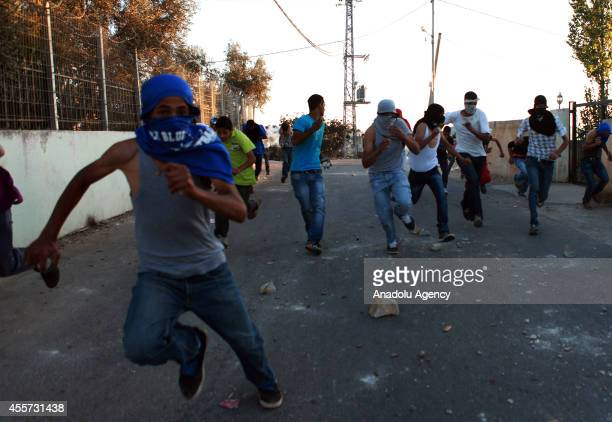 Palestinian youths run seek for cover from tear gas fired by Israeli soldiers during clashes following a protest against the Jewish settlements and...
