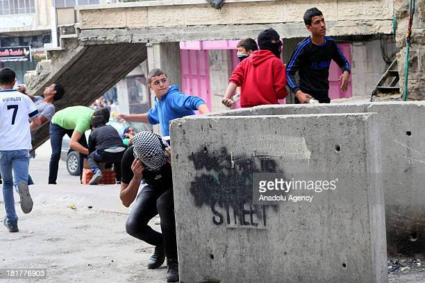 Palestinian youths throw stones at Israeli soldiers as Jewish settlers erect a protest tent in front of the house of the Palestinian Abu Rajab family...
