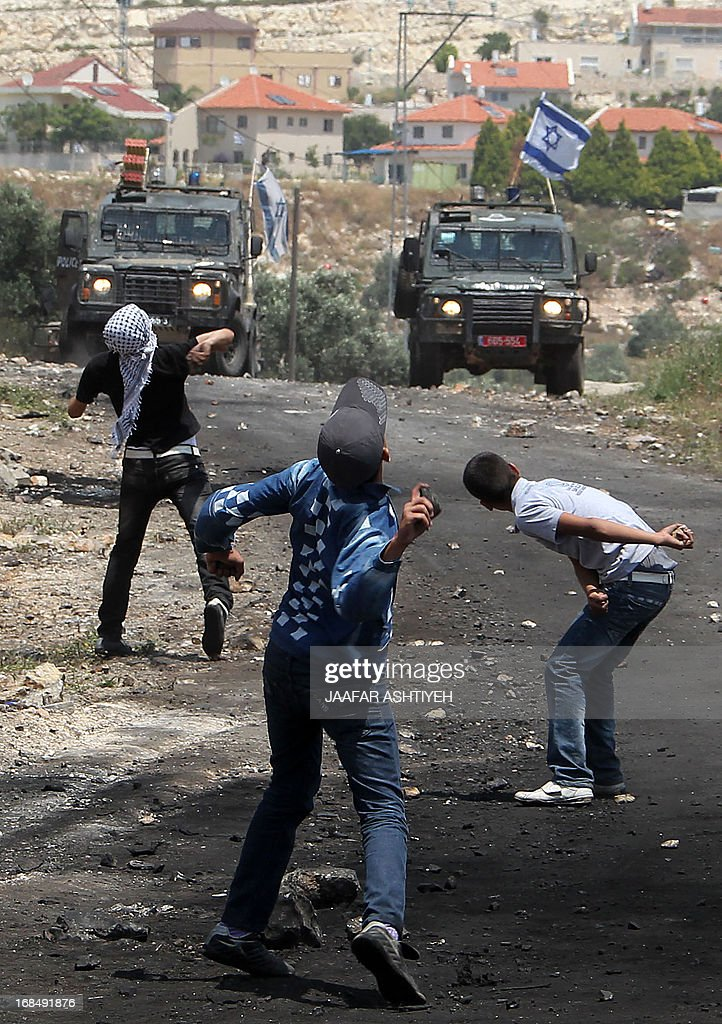 Palestinian youths throw stones towards Israeli troops during clashes following a protest against the expropriation of Palestinian land by Israel in the village of Kfar Qaddum near Nablus in the occupied West Bank on May 10, 2013.