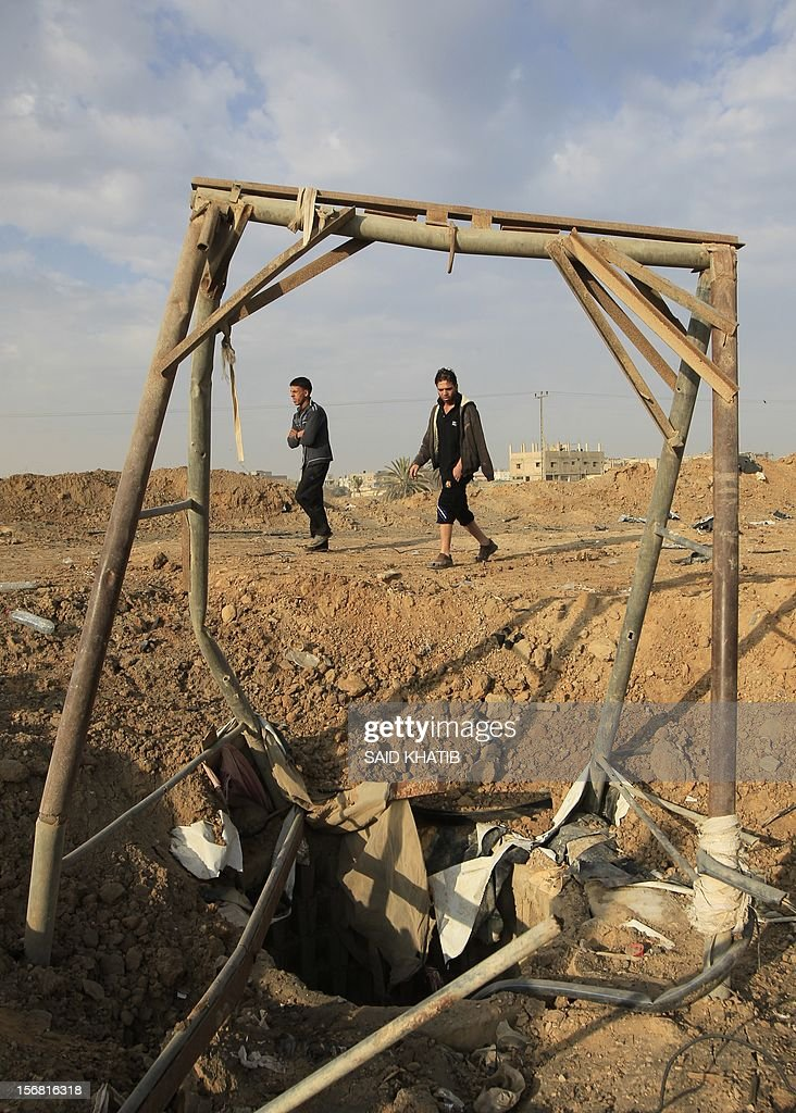 Palestinian youths walk past a crater near bombed smuggling tunnels between the southern Gaza Strip and Egypt in the border town of Rafah on November 22, 2012. A ceasefire took hold in and around Gaza after a week of cross-border violence between Israel and Palestinian militants that killed at least 160 people.