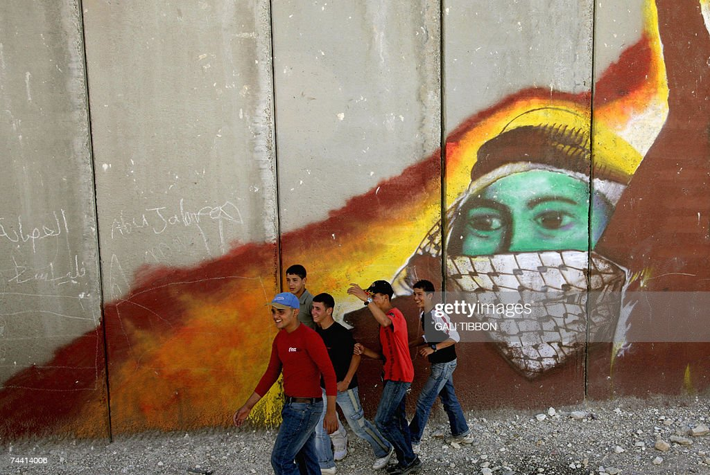 Palestinian youths walk past Israel's controversial separation barrier during a joint IsraeliPalestinian rally in th West Bank village of Anata on...