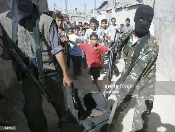 Palestinian youths watch masked Palestinian militant members of the Hamas group walk by while they hold their guns and bombs July 7 2003 in Rafah...