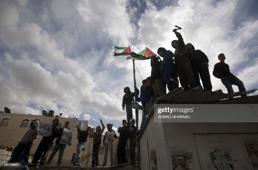Palestinian youths wave their national flag and hold portraits of Samer Issawi, a Palestinian prisoner who has been on hunger strike for more than 200 days in an Israeli pirson, during a demonstration demanding for his release in the Arab east Jerusalem neighbourhood of Issawiya on February 15, 2013. A United Nations official on February 13, expressed concern about the wellbeing of Palestinian detainees in Israeli prisons and in particular about the condition of Issawi.
