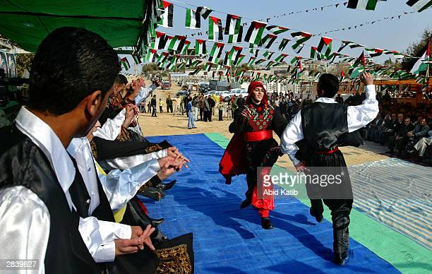 Palestinian youths wearing traditional dress dance a folk dance known as a Dabka during a celebration of the coming New Year January 1 2004 in Gaza...