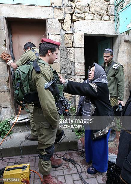 Palestinian Zahira Dandees argues with Israeli soldiers as they seal off the door of her house to prevent her from accessing it after they said a...