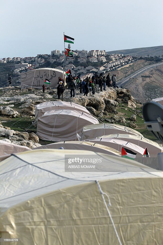 Palestinians alongwith Israeli and foreign activists gather near tents that Palestinians set up in an 'outpost' named Bab al-Shams ('Gate of the Sun') between Jerusalem and the Jewish settlement of Maale Adumim in the Israeli-occupied West Bank, in an area where Israel has vowed to build new settler homes, on January 12, 2013. The Israeli occupation administration gave Palestinian activists an ultimatum to quit the protest camp in part of the West Bank, but hours after the deadline passed, there was no sign of any Israeli move to evict the protesters. AFP PHOTO/ABBAS MOMANI