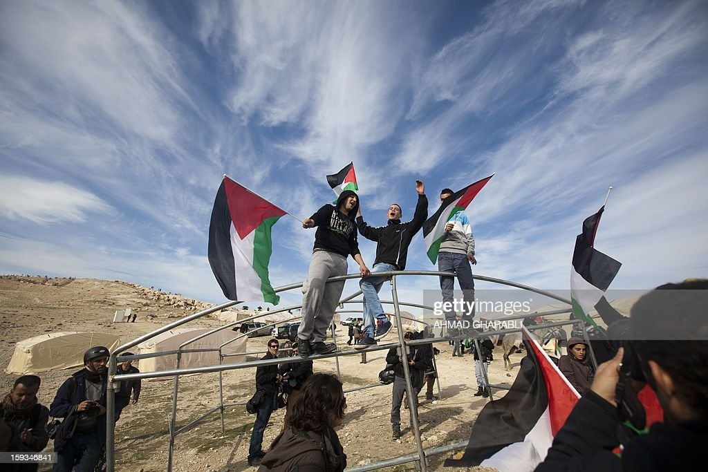 Palestinians alongwith Israeli and foreign activists wave Palestinian flags shouting slogans during a gathering at an 'outpost' named Bab al-Shams ('Gate of the Sun') between Jerusalem and the Jewish settlement of Maale Adumim in the Israeli-occupied West Bank, in an area where Israel has vowed to build new settler homes, on January 12, 2013. The Israeli occupation administration gave Palestinian activists an ultimatum to quit the protest camp in part of the West Bank, but hours after the deadline passed, there was no sign of any Israeli move to evict the protesters.