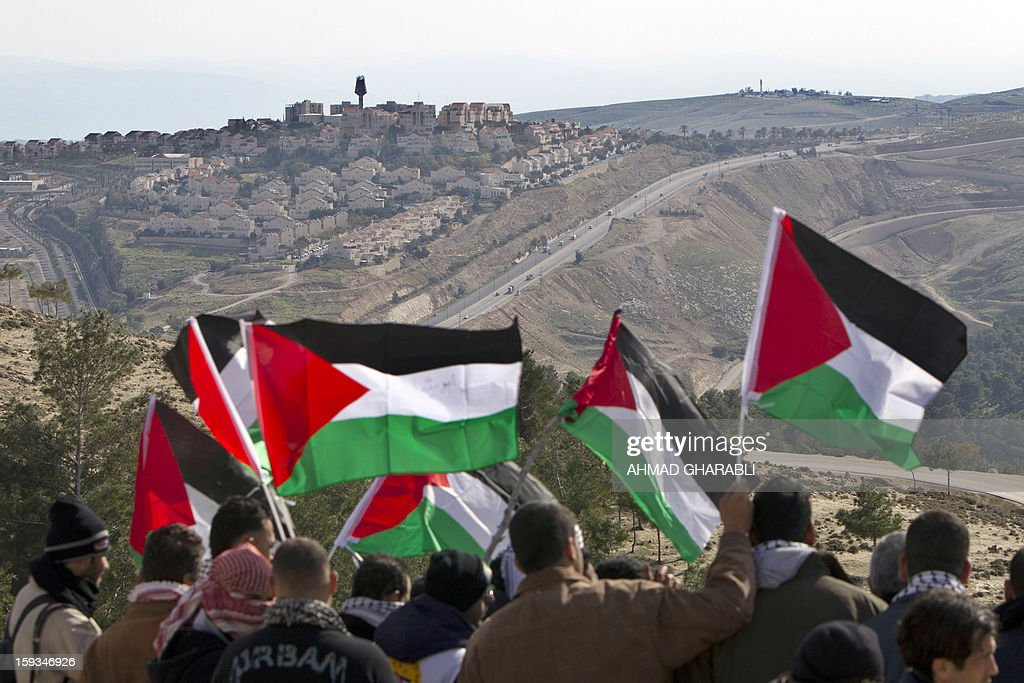 Palestinians alongwith Israeli and foreign activists wave Palestinian flags shouting slogans during a gathering at an 'outpost' named Bab al-Shams ('Gate of the Sun') between Jerusalem and the Jewish settlement of Maale Adumim in the Israeli-occupied West Bank, in an area where Israel has vowed to build new settler homes, on January 12, 2013. The Israeli occupation administration gave Palestinian activists an ultimatum to quit the protest camp in part of the West Bank, but hours after the deadline passed, there was no sign of any Israeli move to evict the protesters. AFP PHOTO/AHMAD GHARABLI