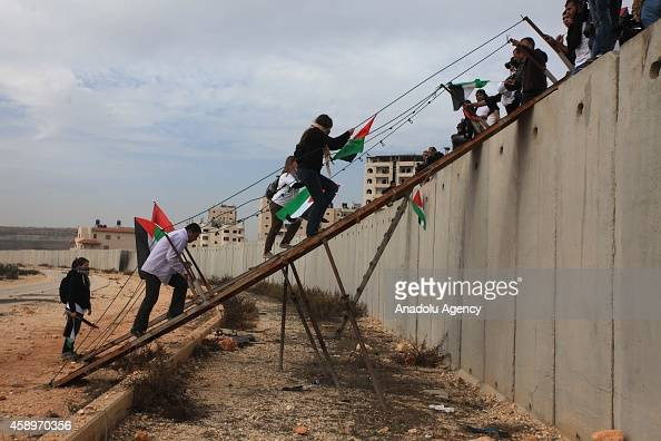 Palestinians and activists from different countries cross the West Bank barrier wall to protest Israeli Government's entrance restriction to the...