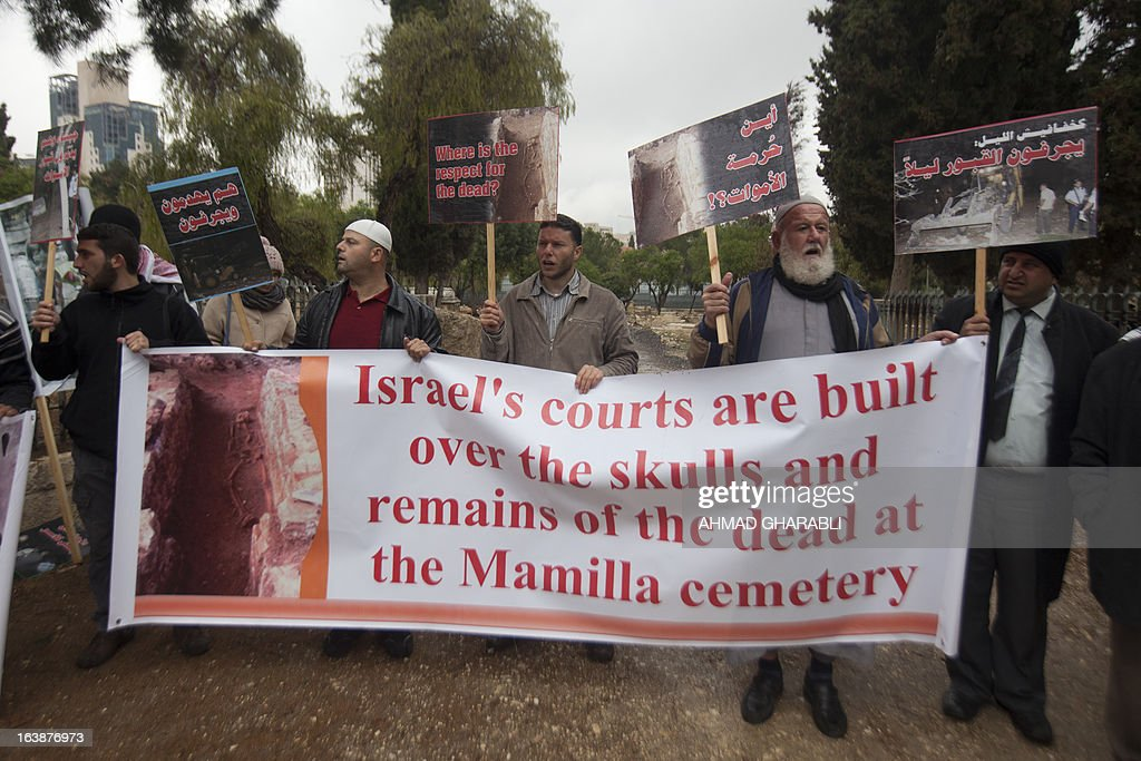 Palestinians and Arab-Israelis hold a banner and placards during a demonstration against the construction of a 'Museum of Tolerance' on the site of an old Muslim cemetery, Mamun Allah, on March 17, 2013 in Jerusalem. The project, organized by the Simon Wiesenthal Center, is the subject of a lengthy legal battle, with Palestinians and some Israeli supporters arguing the museum would desecrate the burial site. Israel's interior ministry approved the start of work in july 2011. AFP PHOTO / AHMAD GHARABLI