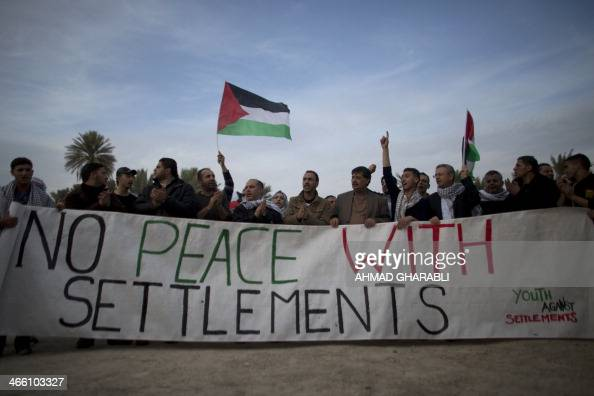 Palestinians and Israeli activists hold a banner reading 'No peace with settlements' as they take part in a protest denouncing the repeated refusals...