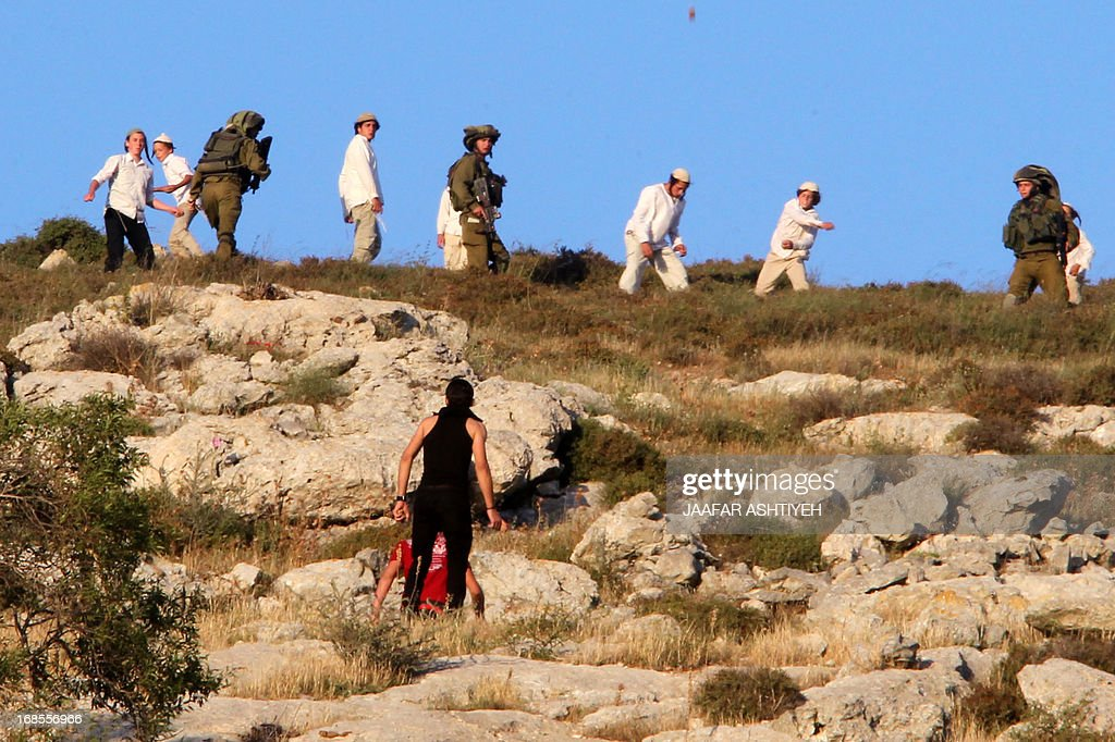 Palestinians and Israeli settlers hurl stones at each other during clashes in the northern West Bank village of Burin on May 11, 2013 after the settlers marched into the village, witnesses said. ASHTIYEH