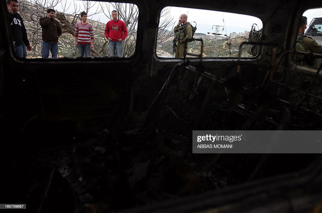 Palestinians and Israeli soldiers inspect a burnt vehicle following an apparent price tag attack by Jewish settlers in the West Bank village of Deir Jarir, northeast of Ramallah, on February 5, 2013. Suspected Jewish extremists torched a vehicle and scrawled Hebrew graffiti on a nearby wall in the village, Palestinians and Israelis said.