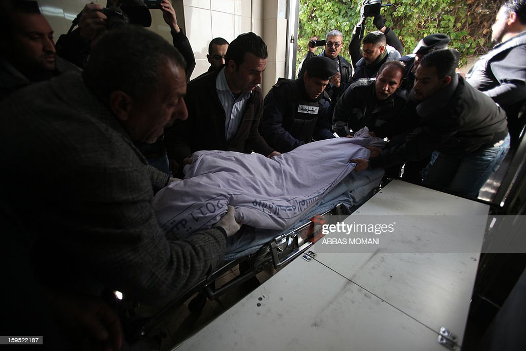 Palestinians and police lift the body of Samir Ahmed Awad, 17, who was shot by Israeli troops not far from Israel's controversial separation barrier, at a morgue near the West Bank city of Ramallah on January 15, 2013. Samir Ahmed Awad died after being hit by a bullet to the chest and another to the leg in an area not far from the village of Ras Karkar, some 10 kilometres (about six miles) northwest of Ramallah, Palestinian medical and security sources told AFP.