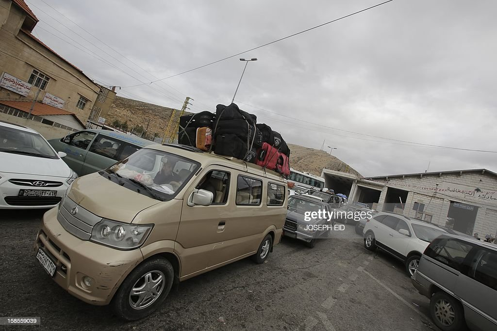 Palestinians and Syrians who fled violence in their country are seen at the Masnaa Lebanese border crossing with Syria as people stamp their documents before entering Lebanon on December 19, 2012. A large number of Palestinians refugees and others who fled the Damascus suburb of Yarmuk and the Yarmuk refugee camp arrived at the border crossing fleeing the fighting in and around their district. According to the United Nations agency for Palestinian refugees the population of the refugee camp has halved as Syrian rebels made advances in a fierce battle for control of the camp in southern Damascus the Syrian Observatory for Human Rights said. AFP PHOTO /JOSEPH EID