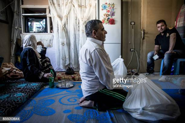Palestinians are pictured inside their refuge home in the Beqaa Valley receiving food parcels They are refugees twice over having fled Palestine and...